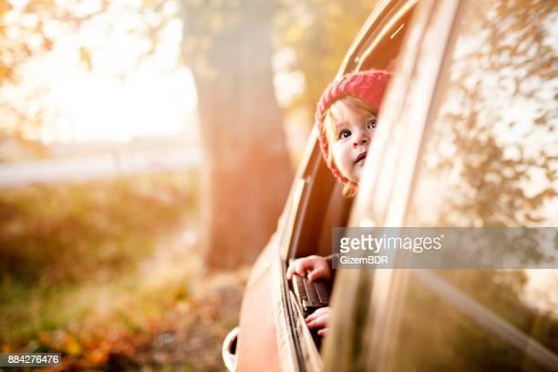 de kleine jongen kijkt uit het raam van de auto