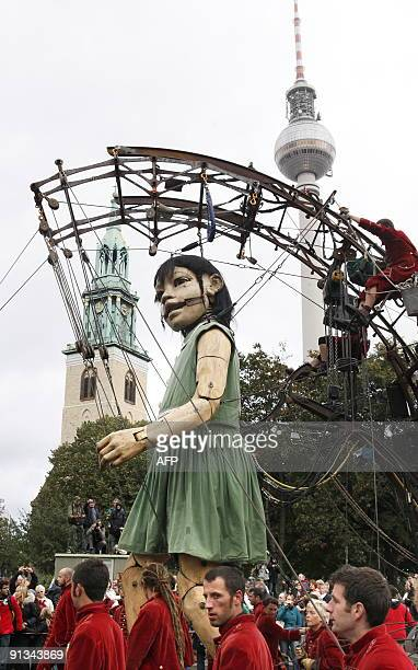The Little Giantess of the French theatre company Royal de Luxe walks in past Berlin's TV tower on October 2 2009 on the first day of the giant's...