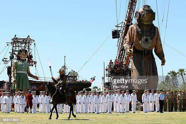 The Little Girl and Diver Giant's look on as a flame of rememberance is carried on horse back for an ANZAC ceremony during the Perth International...