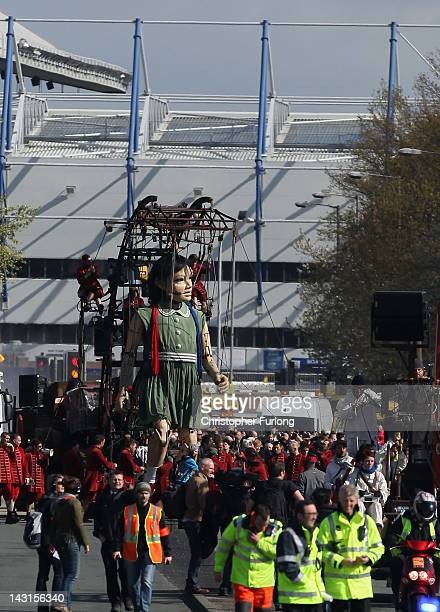 The Little Girl Giant Marionette makes it's way past Everton Football Club through the streets of Liverpool as the Titanic Sea Odyssey giant puppet...