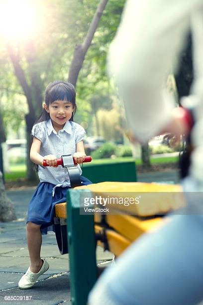 The little girl playing on the seesaw
