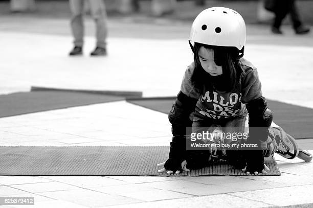 The little girl takes a roller-blading, but falls to the ground.