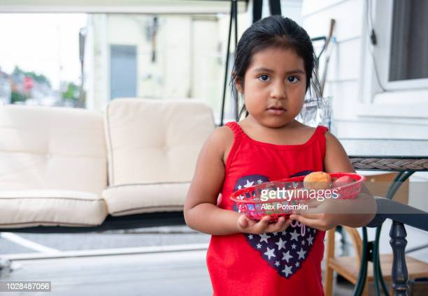 The little Latino Mexican-American girl holding the plate with fruits at the porch of his house