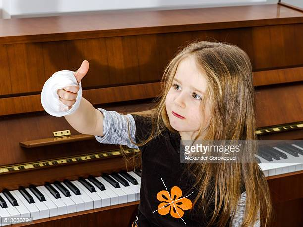 the little optimistic pianist despite the broken hand - elastic bandage stock photos and pictures