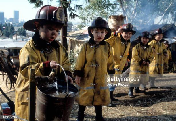 The Little Rascals wearing firemen suits and fetching water in a scene from the film 'The Little Rascals' 1994