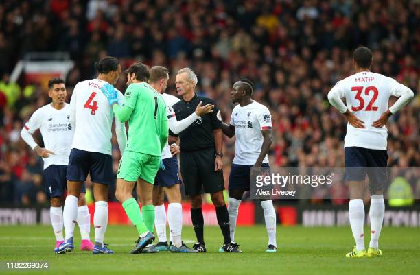 The Liverpool side surround Match Referee Martin Atkinson as Marcus Rashford of Manchester United scores his sides first goal during the Premier...