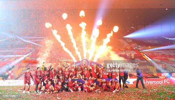 The Liverpool Team celebrate on the pitch after winning the Premier League Title during the presentation ceremony of the Premier League match between...