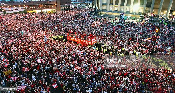 The Liverpool team ride on an open top bus through a mass of fans as they arrive at St George's Hall during the Liverpool Champions League Victory...