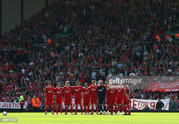 The Liverpool team stand for the minute silence for the victims of the Hillsborough disaster prior to the Barclays Premier League match between...