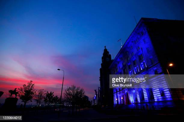 The Liverpool waterfront lights up blue at sunset alongside the Royal Liver Buildings on April 23 2020 in Liverpool United Kingdom Following the...