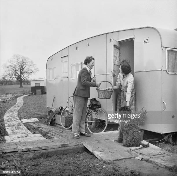 The local butcher's wife delivering supplies to Mrs Glover, living in a caravan on a temporary site at Berkeley Nuclear Power Station during its...