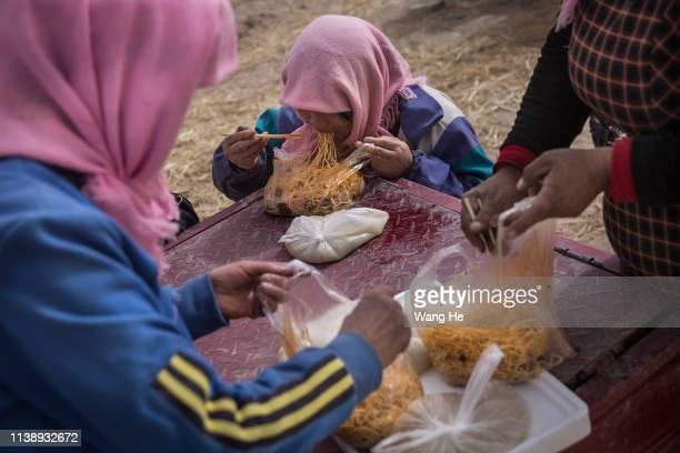 The local women eat noodle after planting saxaul in the desert at Mingqin county on March 27th 2019 in Wuwei Gansu Province China In order to prevent...