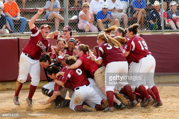 The Lock Haven University softball team mobs their catcher at home plate as they celebrate their second championship in four years at the Division II...