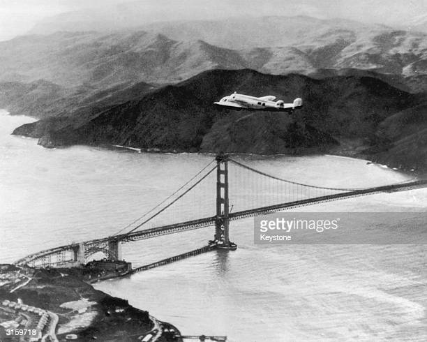 The Lockheed Electra 'Flying Laboratory' piloted by American aviator Amelia Earhart and Fred Noonan flies over the Golden Gate bridge in Oakland...