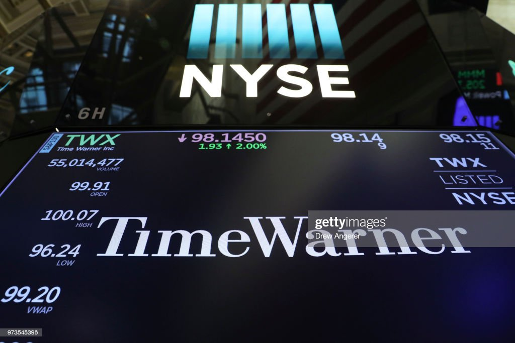 The logo and trading information for Time Warner is displayed on a monitor on the floor of the New York Stock Exchange (NYSE) June 13, 2018 in New York City. Following news today that the Federal Reserve raised interest rates a quarter percentage point, the Dow Jones Industrial Average was down 119 points at the close.