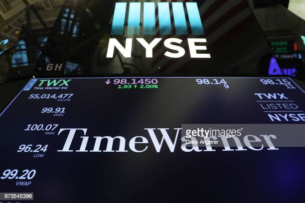 The logo and trading information for Time Warner is displayed on a monitor on the floor of the New York Stock Exchange June 13 2018 in New York City...