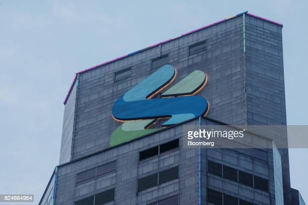 The logo for Standard Chartered Plc is displayed atop the Standard Chartered Bank building in Hong Kong China on Sunday July 30 2017 Standard...