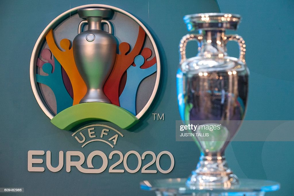 The logo for the UEFA European Championship football competition (L) is displayed next to the Euros trophy (R) during a launch event in London on September 21, 2016. The 2020 UEFA European Championship will see matches hosted in 13 cities across Europe, with the semi-finals and final staged at Wembley Stadium in London in July 2020. / AFP / JUSTIN