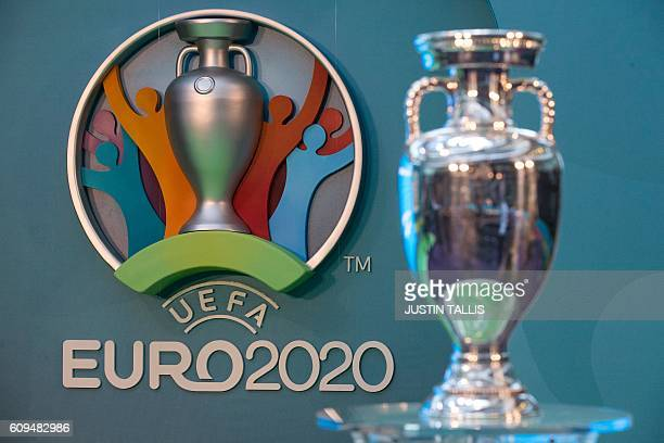 The logo for the UEFA European Championship football competition is displayed next to the Euros trophy during a launch event in London on September...