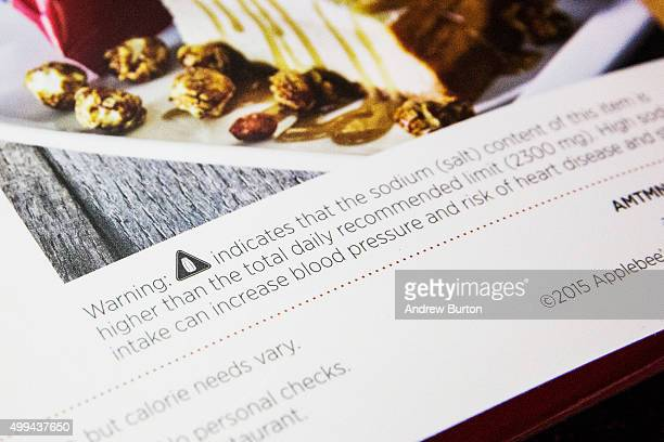 The logo of a salt shaker meant to warn consumers of high sodium content in food appears on an Applebees menu on December 1 2015 in New York City The...