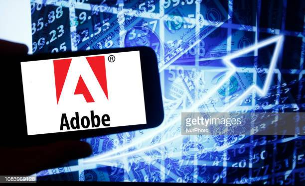 The logo of Adobe Systems is seen on a screen of a smartphone next to a screen with an illustration ofthe stock market Adobe is listed in Nasdaq The...