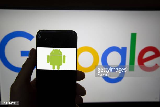The logo of Android is seen on a screen. In the background there is the logo of Google. Alphabet is the mother company of Google. It has a revenue of...