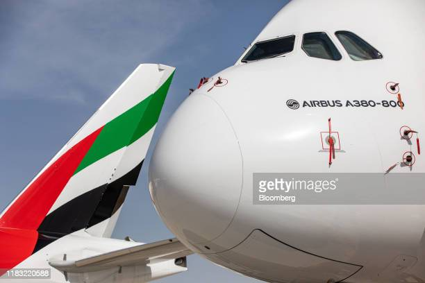 The logo of Emirates Airline sits on the tailfin of a Boeing Co. 777-300 aircraft, parked near an Airbus SE A380-800 aircraft on the first day of the...