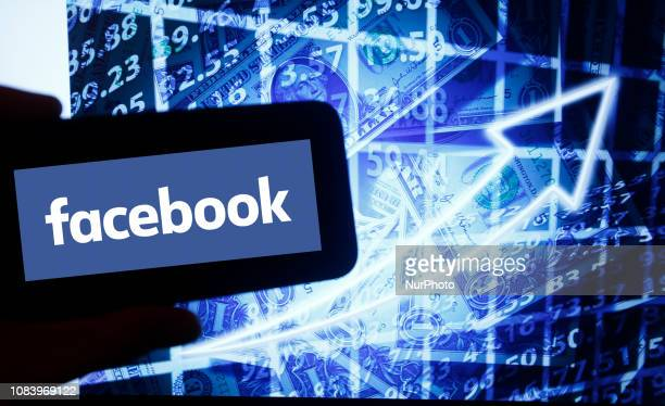 The logo of facebook is seen on a screen of a smartphone next to a screen with an illustration ofthe stock market Facebook is listed in Nasdaq The...