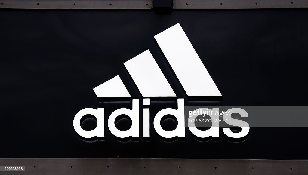 The logo of German sport brand Adidas is pictured on a store in Berlin on January 25, 2016. / AFP / TOBIAS