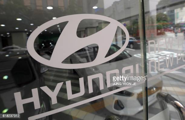 The logo of Hyundai Motor is seen on a glass door at a dealership in Seoul on October 26 2016 South Korea's Hyundai Motor on October 26 announced a...