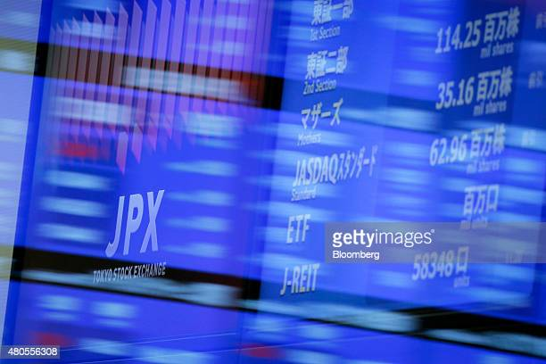 The logo of Japan Exchange Group Inc the operator of the Tokyo Stock Exchange is displayed on an electric stock board seen through glass panels at...