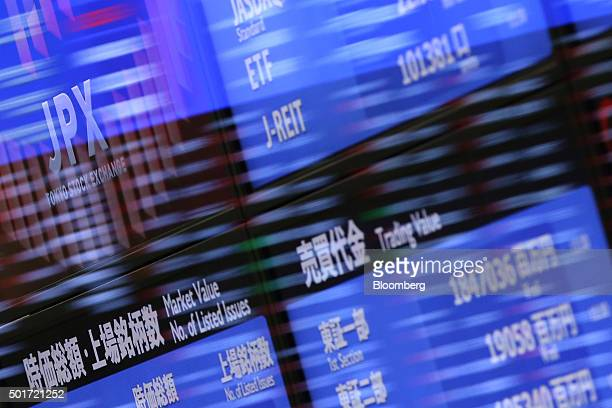 The logo of Japan Exchange Group Inc the operator of the Tokyo Stock Exchange is displayed on an electric board seen through glass panels reflecting...