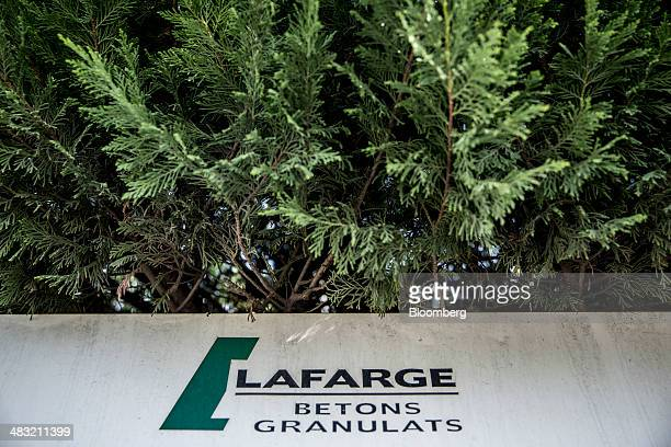 The logo of Lafarge SA sits on a sign at the company's distribution center in Albi France on Monday April 7 2014 Holcim Ltd and Lafarge SA agreed a...