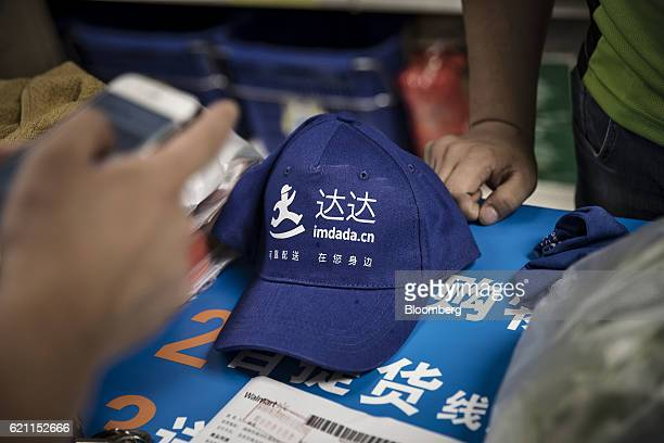 The logo of New Dada Chinas largest logistics and grocery ecommerce platform partially owned by JDcom Inc is seen on a hat in a WalMart Stores Inc...