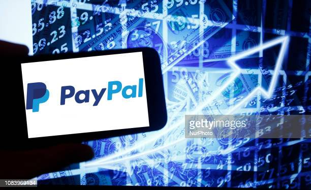 The logo of PayPal is seen on a screen of a smartphone next to a screen with an illustration of the stock market. PayPal is listed in Nasdaq. The...