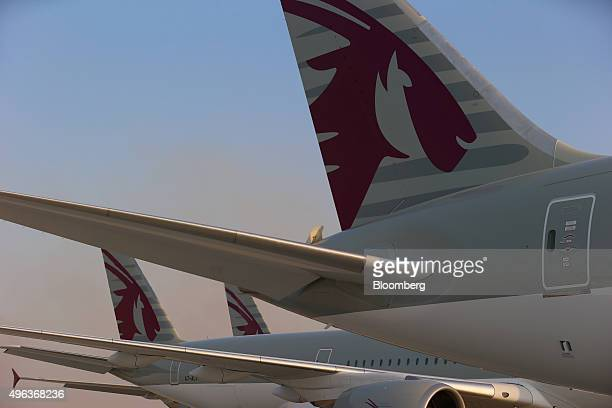 The logo of Qatar Airways Ltd sits on the tail fins of display aircraft including a Boeing 787800 Dreamliner manufactured by Boeing Co right an...