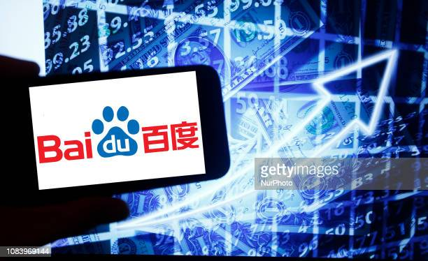 The logo of the Chinese technology corporation Baidu is seen on a screen of a smartphone next to a screen with an illustration ofthe stock market....