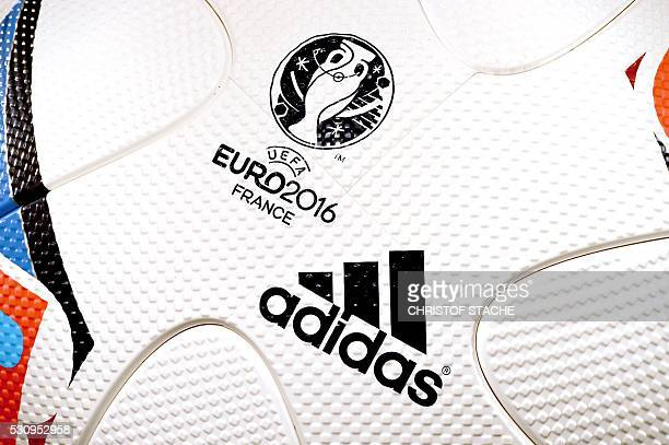 The logo of the German sportswear giant Adidas and the official symbol of the UEFA Euro 2016 football championships in France is seen on an official...