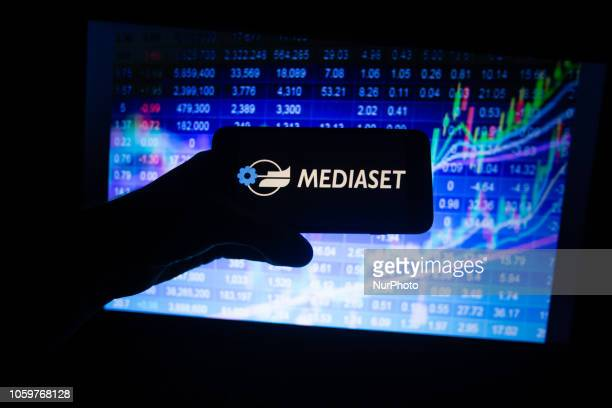 The logo of the Italian company Mediaset listed in the MIB in Milan is seen on a screen In the background there is a colorful stock exchange price...