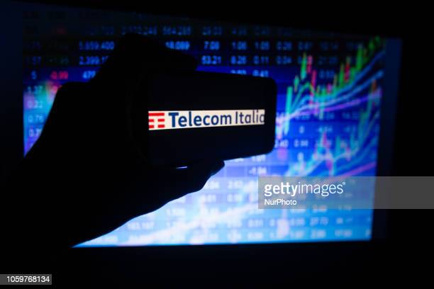 The logo of the Italian company Telecom Italia listed in the MIB in Milan is seen on a screen In the background there is a colorful stock exchange...