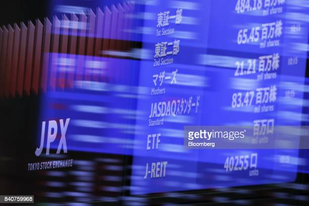 The logo of the Japan Exchange Group Inc on an electric stock board is seen through glass panels at the Tokyo Stock Exchange in Tokyo Japan on...