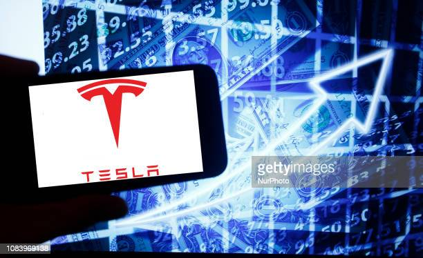 The logo of the Tesla Inc is seen on a screen of a smartphone next to a screen with an illustration ofthe stock market Tesla is listed in Nasdaq The...