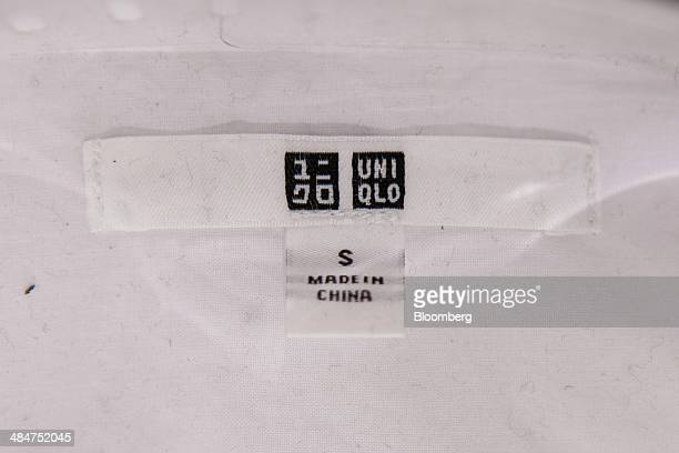 The logo of Uniqlo sits above a made in China label on an item of clothing on sale inside a Uniqlo store the fashion clothing retailer operated by...