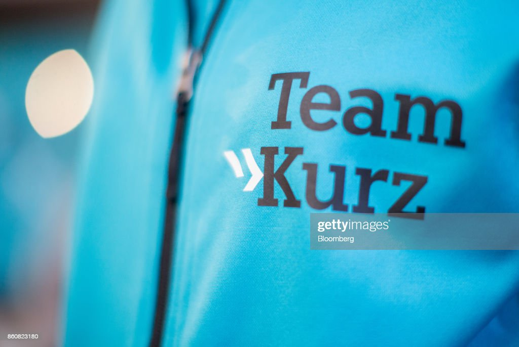 The logo 'Team Kurz' sits on the jacket of a supporter as Sebastian Kurz, Austria's foreign minister and leader of the People's Party (OeVP), not pictured, speaks during his final campaign event in Vienna, Austria, on Friday, Oct. 13, 2017. The front-running Peoples Party shifted toward the Freedom Partys hard-line immigration stance, yet on the economy both parties hew to Germanys penchant for tight budgets in the euro area. Photographer: Lisi Niesner/Bloomberg via Getty Images