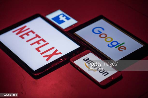 The logos for Facebook Inc Amazoncom Inc Netflix Inc and Google a unit of Alphabet Inc sit on smartphone and tablet devices in this arranged...