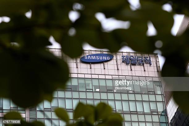 The logos for Samsung Group left and Cheil Industries Inc are displayed atop the Cheil Industries office building in Seoul South Korea on Friday June...