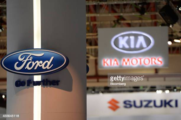 The logos of Ford Motor Co Kia Motors Corp and Suzuki Motor Corp are displayed at the Indonesia International Motor Show in Jakarta Indonesia on...