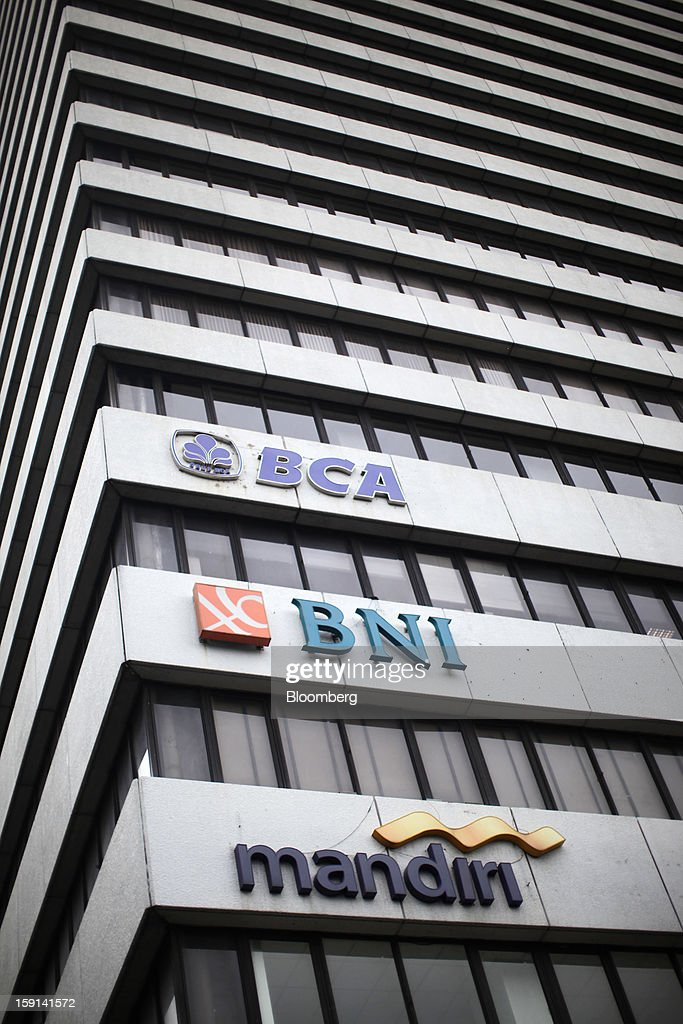 The logos of PT Bank Central Asia (BCA), PT Bank Negara Indonesia (BNI) and PT Bank Mandiri are displayed outside a building in the financial district of Jakarta, Indonesia, on Tuesday, Jan. 8, 2013. Indonesia's rupiah weakened by the most in six months on concern the government's failure to meet its spending target last year will hamper economic growth and damp demand for local assets. Photographer: Dimas Ardian/Bloomberg via Getty Images