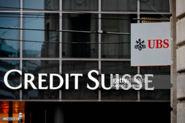 The logos of Switzerland banking giants Credit Suisse and UBS are seen on December 5 2014 in the city of Basel AFP PHOTO / FABRICE COFFRINI
