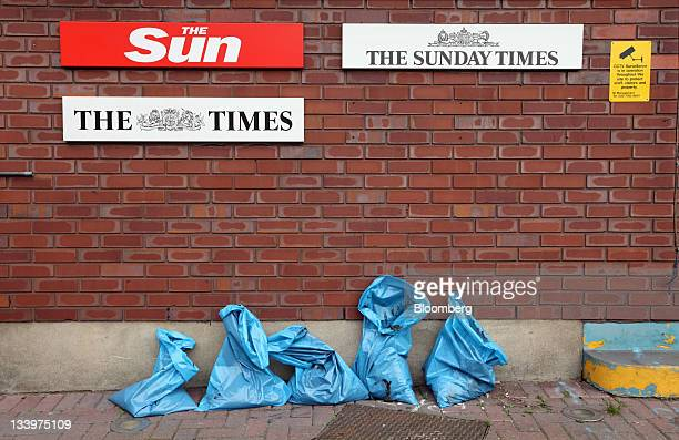 The logos of The Sun, The Times and The Sunday Times newspapers, published by News Corp.'s U.K. News International division, are seen outside the...